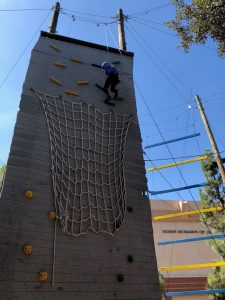 A student climbing a rock wall obstacle