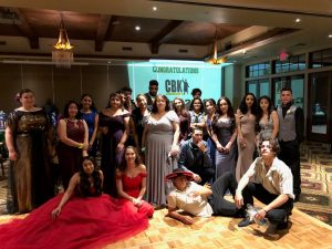Group of students posing in prom dresses and tuxedos